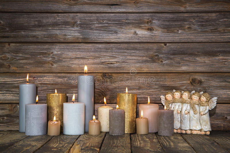 Christmas greeting card with candles and angels on wooden background. royalty free stock image