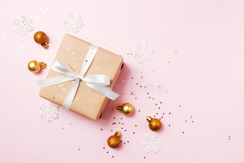 Christmas greeting card composition. Craft paper gift with white ribbon on pink background with christmas golden balls and royalty free stock image