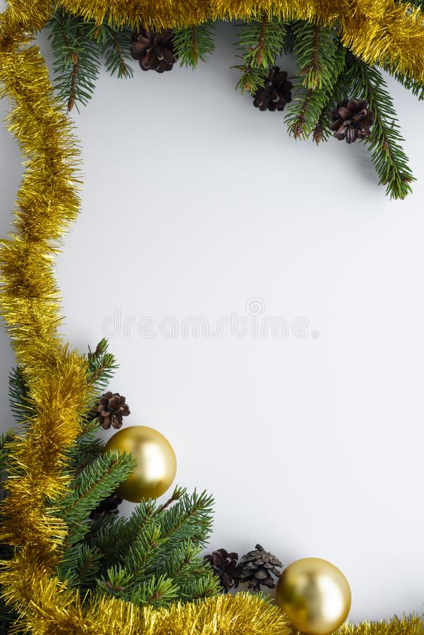 Christmas greeting card with copy space. Vertical set up of festive decorations such as gold baubles, tinsel, conifer tree. Christmas greeting card with copy royalty free stock image