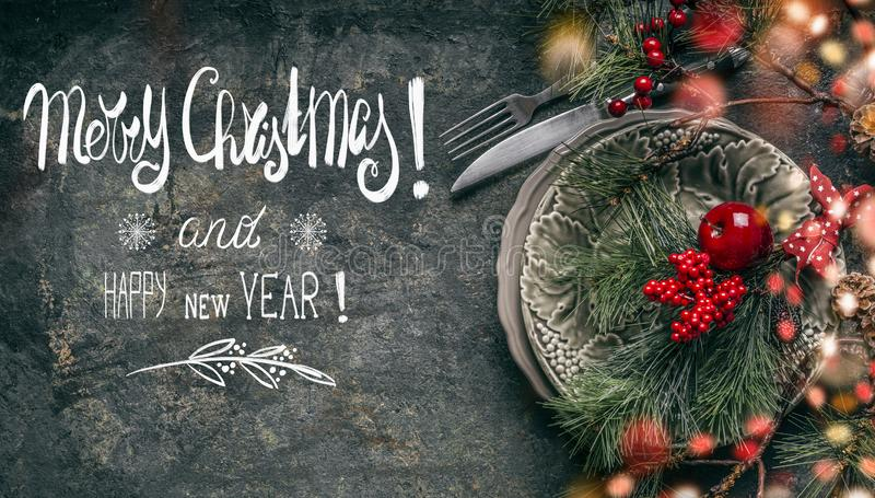 Festive table place setting decoration on dark rustic background with text lettering: Merry Christmas and Happy New Year. Christmas greeting card with festive stock photos