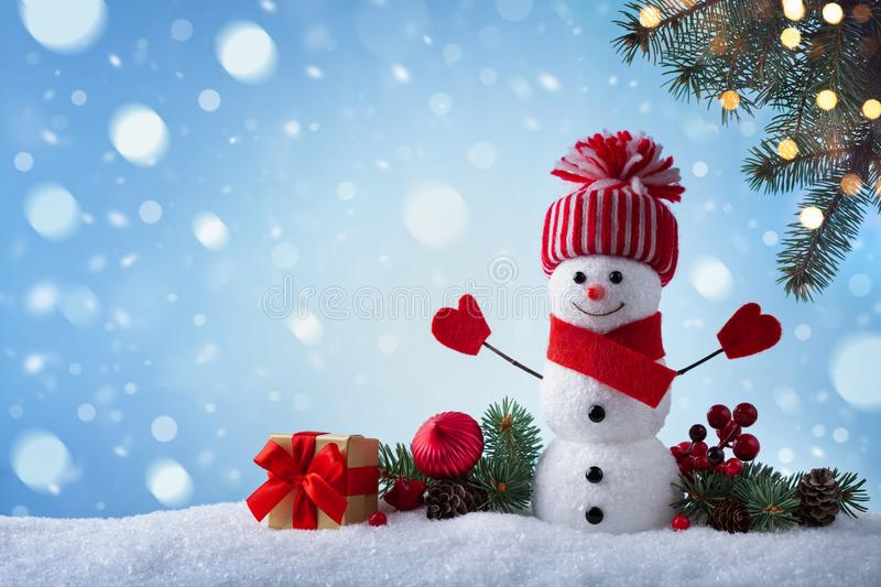 Christmas greeting card with funny snowman, gift box and fir tree branches in winter scenery. Snowy background stock photo