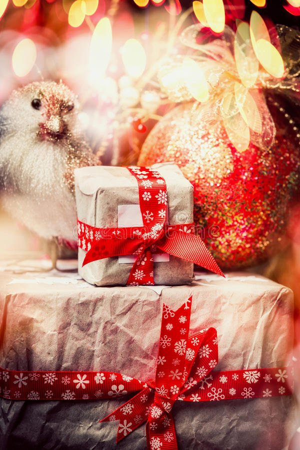 Christmas greeting card with gift boxes tied with a red ribbon, bird at shine holiday decoration and bokeh lighting, vintage stock photography