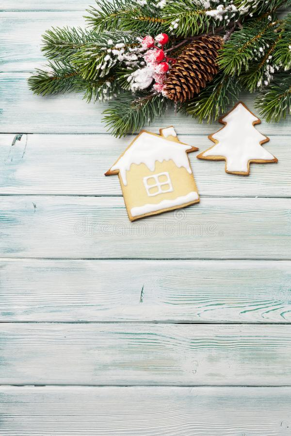 Christmas greeting card with gingerbread cookies. And fir tree on wooden background. Top view with space for your greetings. Flat lay royalty free stock photography