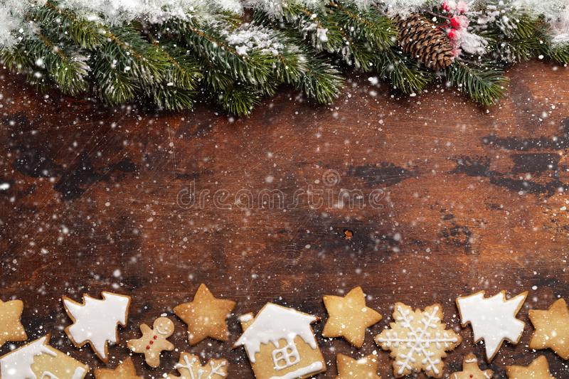 Christmas greeting card with gingerbread cookies. And xmas fir tree branch over wooden backdrop. Top view with space for your greetings royalty free stock image