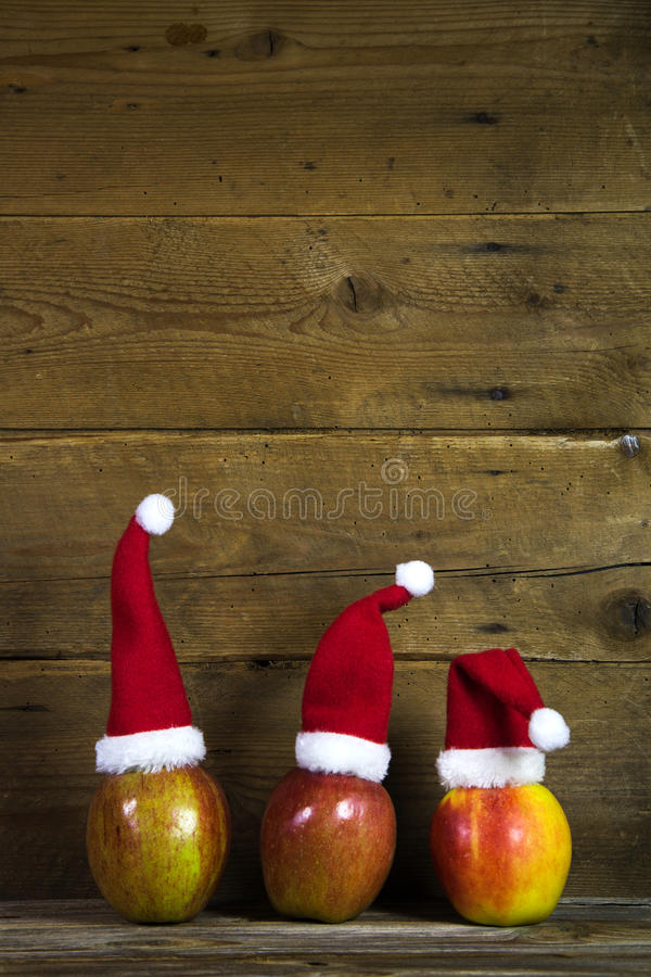 Christmas greeting card with three red santa hats on apples with. Decoration: Funny christmas greeting card with three red santa hats on apples with wooden stock images