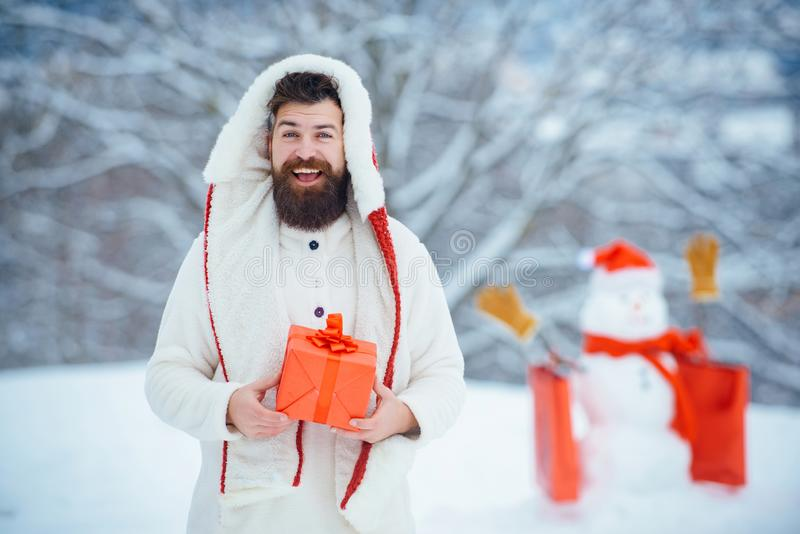 Christmas greeting card. Winter portrait of handsome hipster in snow Garden with gift make snowman. Man with red gift royalty free stock image