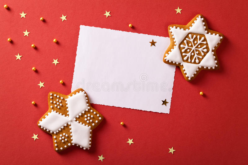 Christmas Greetings. Christmas greeting card with gingerbreads, gold stars and balls. Top view royalty free stock photo