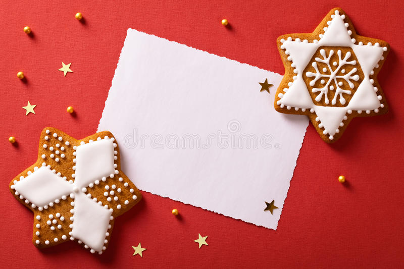 Christmas Greetings. Christmas greeting card with gingerbreads, gold stars and balls. Top view royalty free stock image