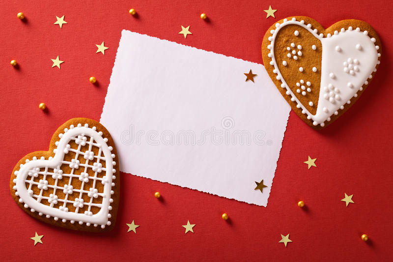 Christmas Greetings. Christmas greeting card with gingerbread hearts, gold stars and balls. Top view stock photos
