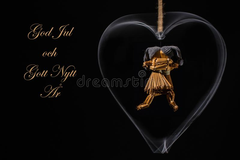 Christmas greetings in Swedish with dancing straw dolls. In a rotating metal heart and with the text: God Jul och Gott Nytt Ã…r =Merry Christmas and Happy royalty free illustration