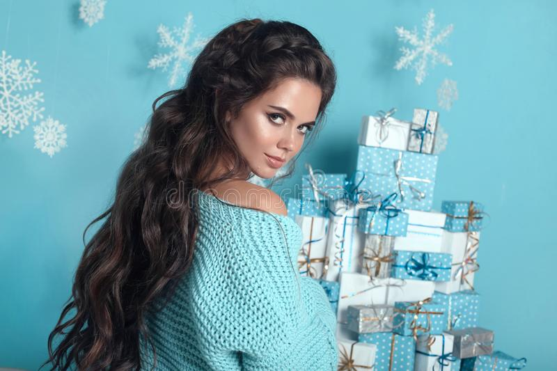 Christmas hairstyle. Portrait of attractive woman with wedding w. Avy hair style. Beautiful brunette girl with long hair wears in warm turquoise woolen sweater royalty free stock photography