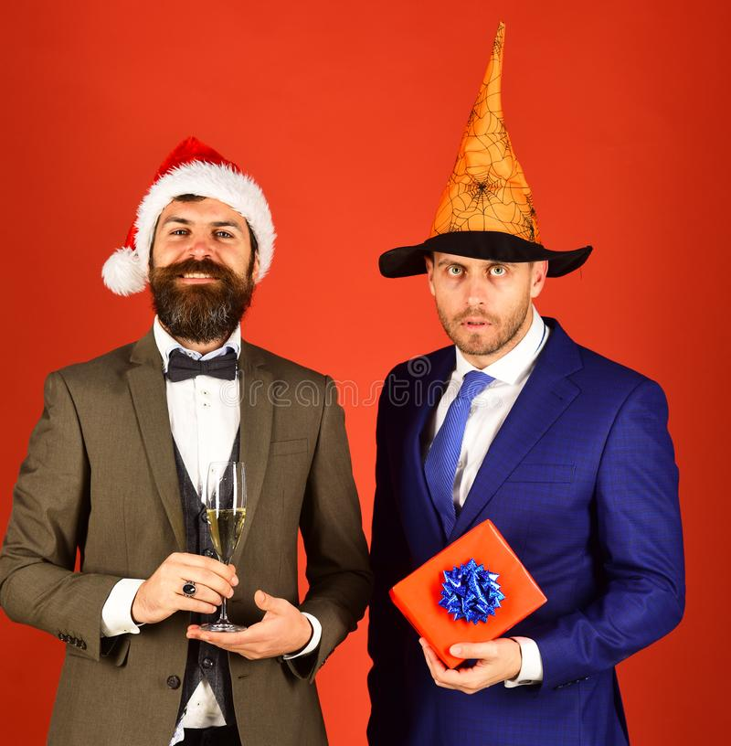 Christmas or Halloween party concept. Men in suits and hats. Christmas or Halloween party concept. Men in suits, Santa and wizard hats on red background royalty free stock photos