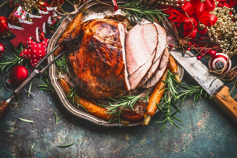 Christmas ham served with roasted vegetables and festive decorations on vintage background in retro color, top view, place for tex. T. Christmas recipes and royalty free stock image