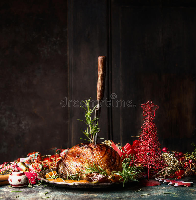 Christmas ham with stuck fork and rosemary on table with festive holiday decoration at wooden background royalty free stock image