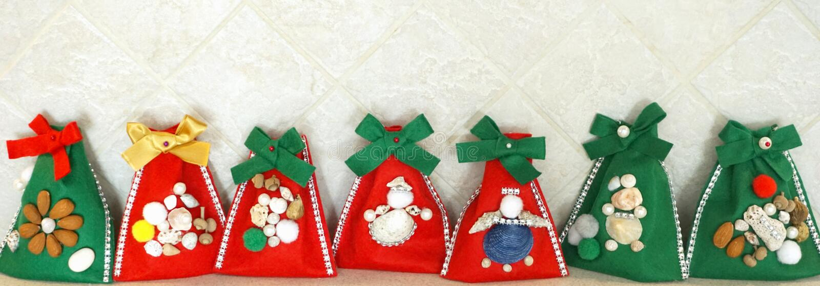 Christmas handmade crafted felt gift bags in line. Christmas homemade green and red felt gift bags in line, decorated with little things royalty free stock photography