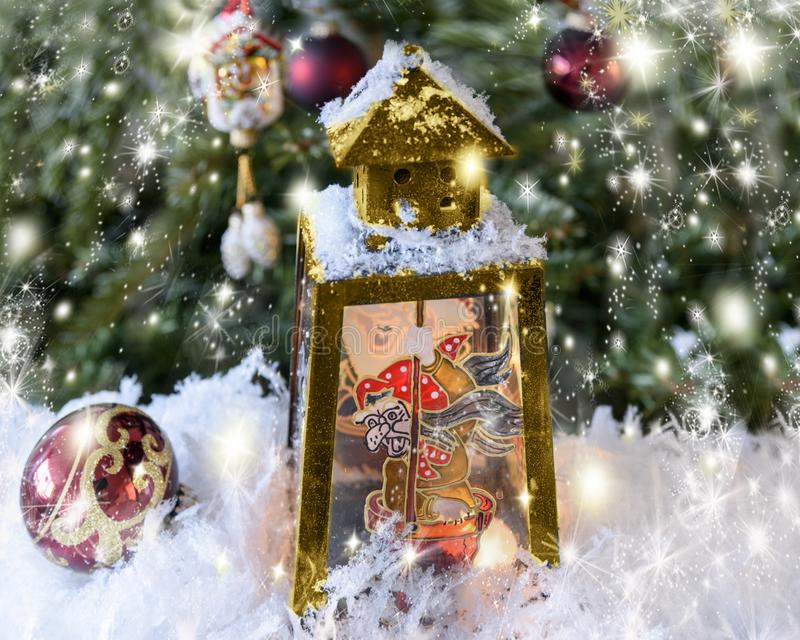 Christmas handmade decorated lantern with a picture of fairy-tale Baba Yaga on the glass. Fir-tree background with lights. New Year`s, Christmas still life stock photo