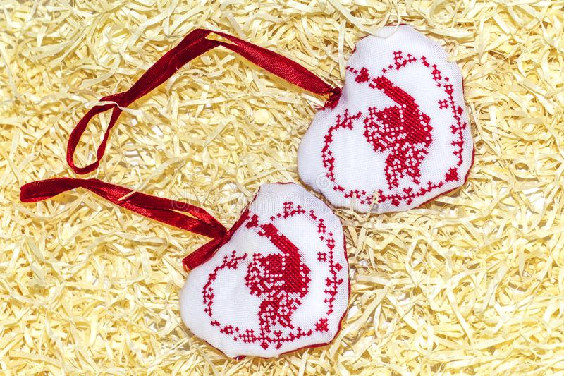 Christmas handmade embroidered decorations soft toys on the straw tinsel  background top view shape of hear, bell, angel, fir tree.  stock image