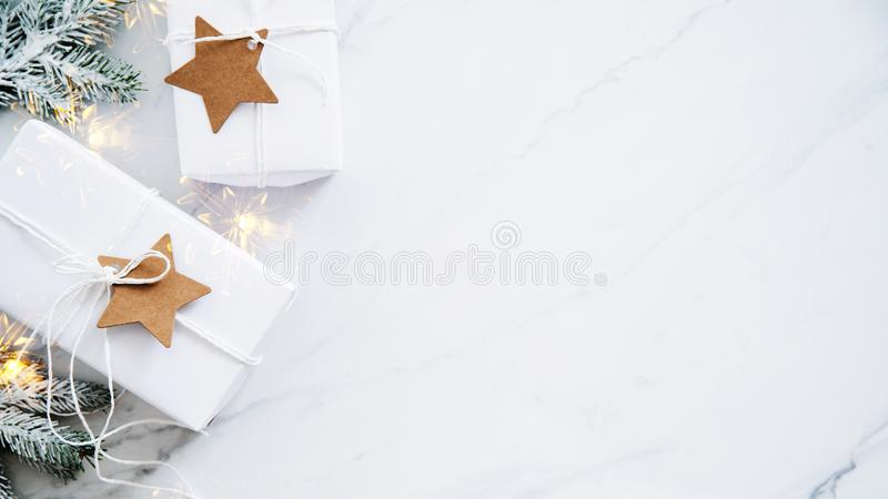 Christmas handmade gift boxes on white marble background top view. Merry Christmas greeting card, frame. Winter xmas holiday theme. Happy New Year. Flat lay royalty free stock photo