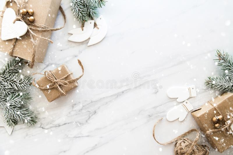 Christmas handmade gift boxes on white marble background top view. Merry Christmas greeting card, frame. Winter xmas holiday theme. Happy New Year. Flat lay stock photography