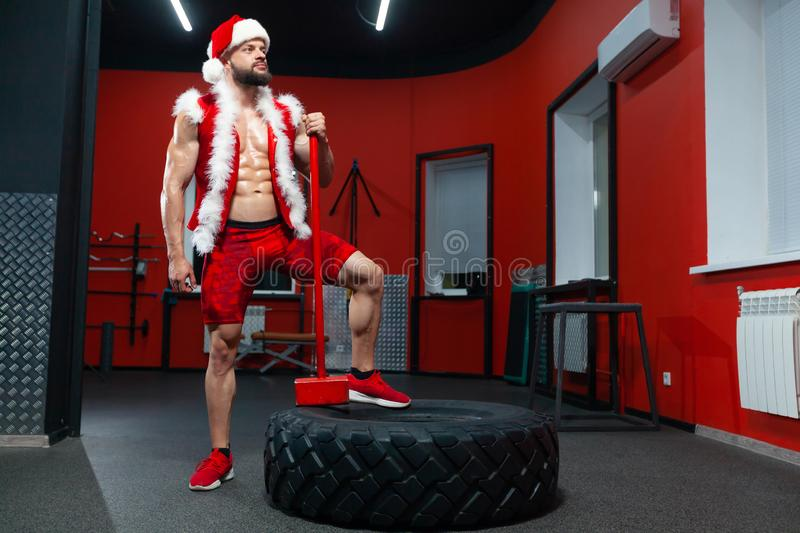Christmas. A handsome muscular man in a red Santa Claus suit with a hammer on the tire performs exercises in the gym. Christmas. A handsome muscular man in a royalty free stock photos