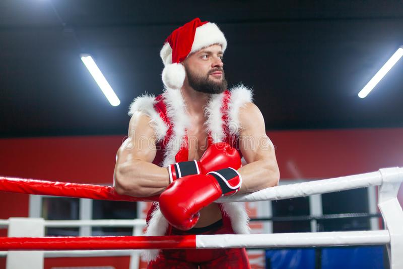 Christmas. A handsome muscular man in a Santa Claus suit with Boxing gloves stands in the ring. GYM. Christmas. A handsome muscular man in a Santa Claus suit royalty free stock photography