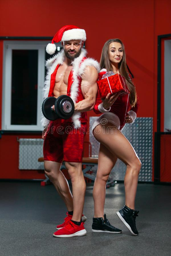 Christmas. Handsome muscular man in Santa Claus suit with dumbbells and fitness woman in red suit with gift . GYM. Christmas. Handsome muscular men in Santa royalty free stock image