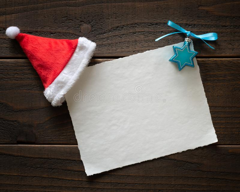 Christmas and Hannukah blank Happy Holidays Card on Rustic Boards with white paper, a Santa hat and Hanukah decoration. It`s horizontal with copy space royalty free stock photos