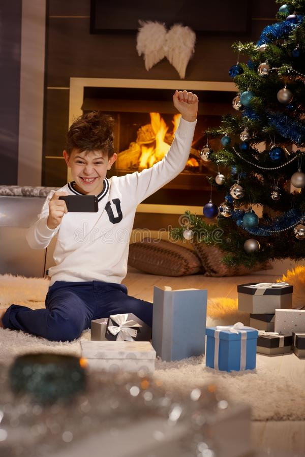 Christmas happiness. Cute schoolboy playing happy with mobilephone at christmas time royalty free stock photography