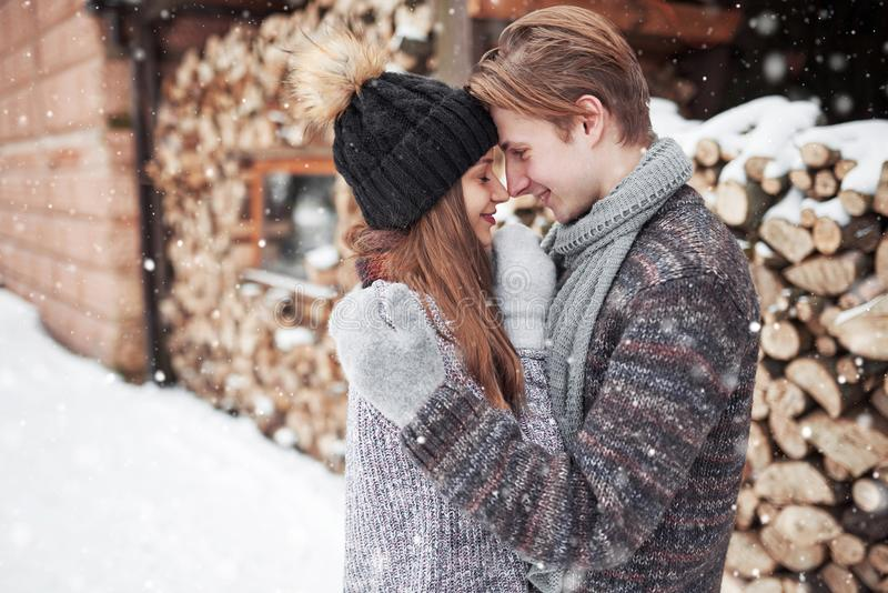Christmas happy couple in love embrace in snowy winter cold forest, copy space, new year party celebration, holiday and royalty free stock photo