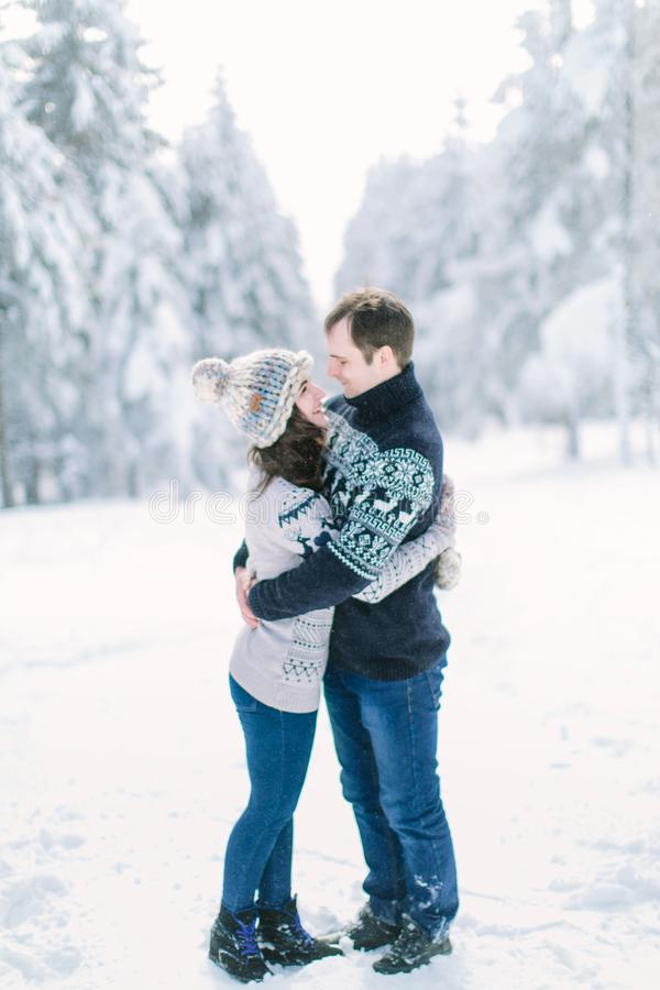 Christmas happy couple in love embrace in snowy winter cold forest, copy space, new year party celebration, holiday and vacation, stock image