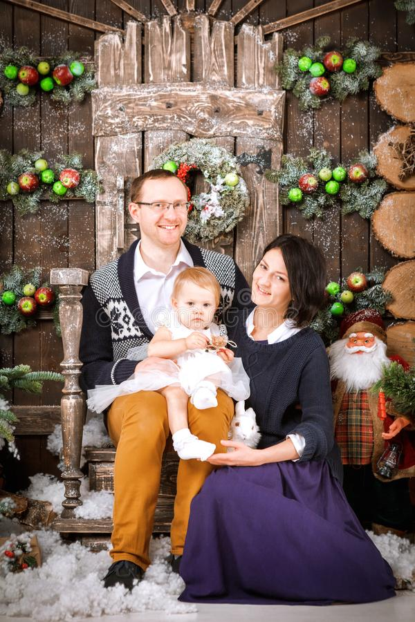 Christmas happy family of three persons and fir tree with gift boxes new year winter decorated background. Christmas family of three persons mother father and royalty free stock photography