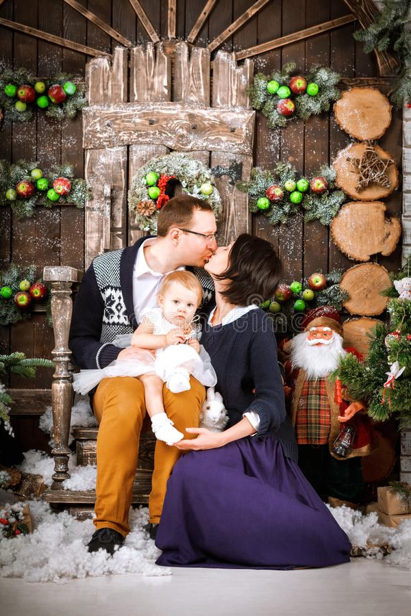Christmas happy family of three persons and fir tree with gift boxes new year winter decorated background. Christmas family of three persons mother father and stock photos