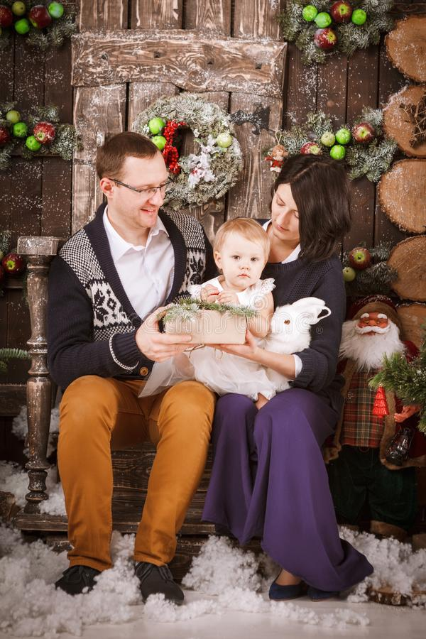 Christmas happy family of three persons and fir tree with gift boxes new year winter decorated background. Christmas family of three persons mother father and stock images