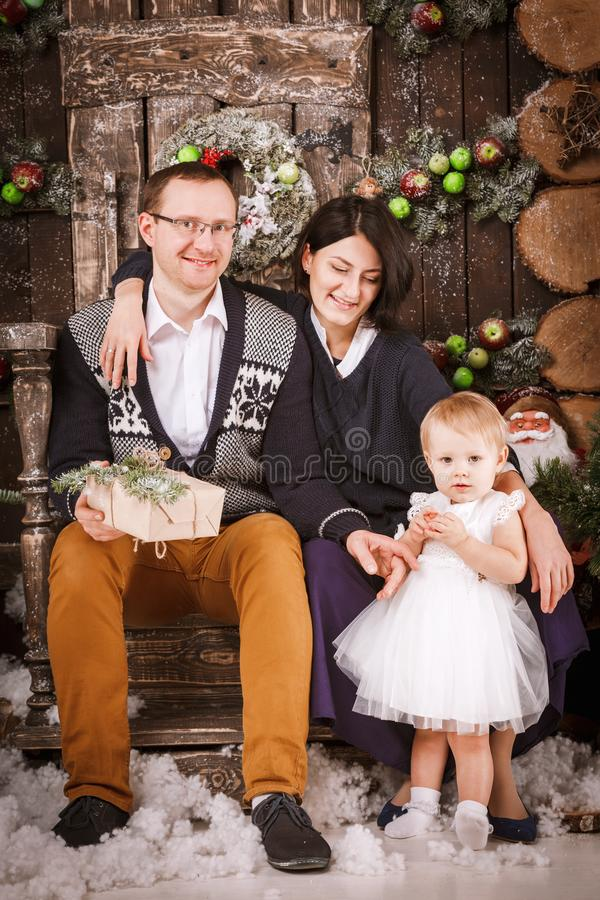 Christmas happy family of three persons and fir tree with gift boxes new year winter decorated background. Christmas family of three persons mother father and royalty free stock photos