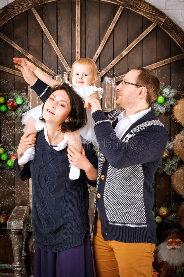 Christmas happy family of three persons and fir tree with gift boxes new year winter decorated background. Christmas family of three persons mother father and stock photography