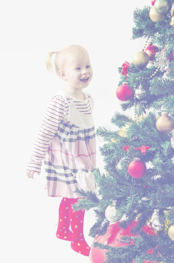 Christmas Happy funny little girl dressing up a Christmas tree on a white background, toned with white. royalty free stock photos