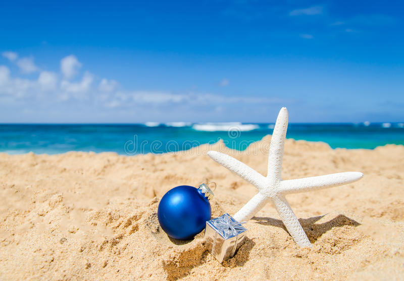 Christmas and Happy New Year background on the tropical beach. Merry Christmas and Happy New Year background with starfish, gift and ball on the tropical beach stock images