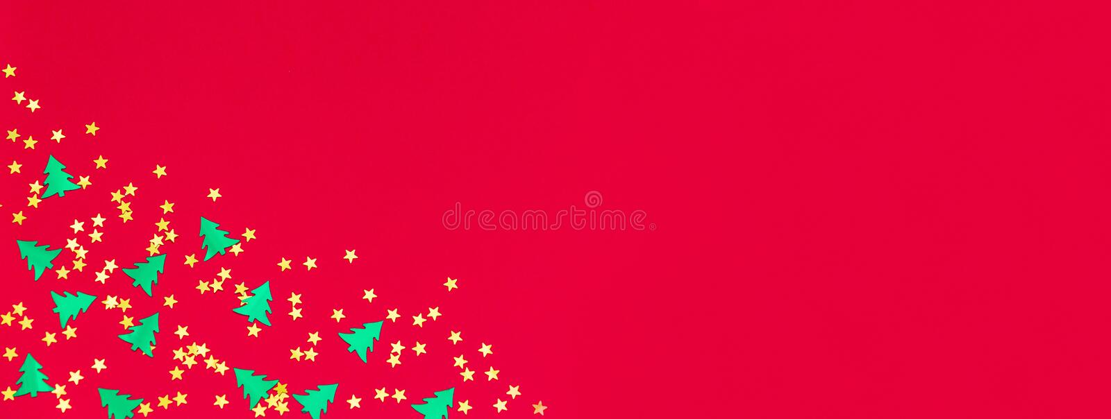 Christmas and Happy new year banner. Green metallic foil christmas trees and gold stars confetti on red background. Simple holiday design template. Frame with royalty free stock image