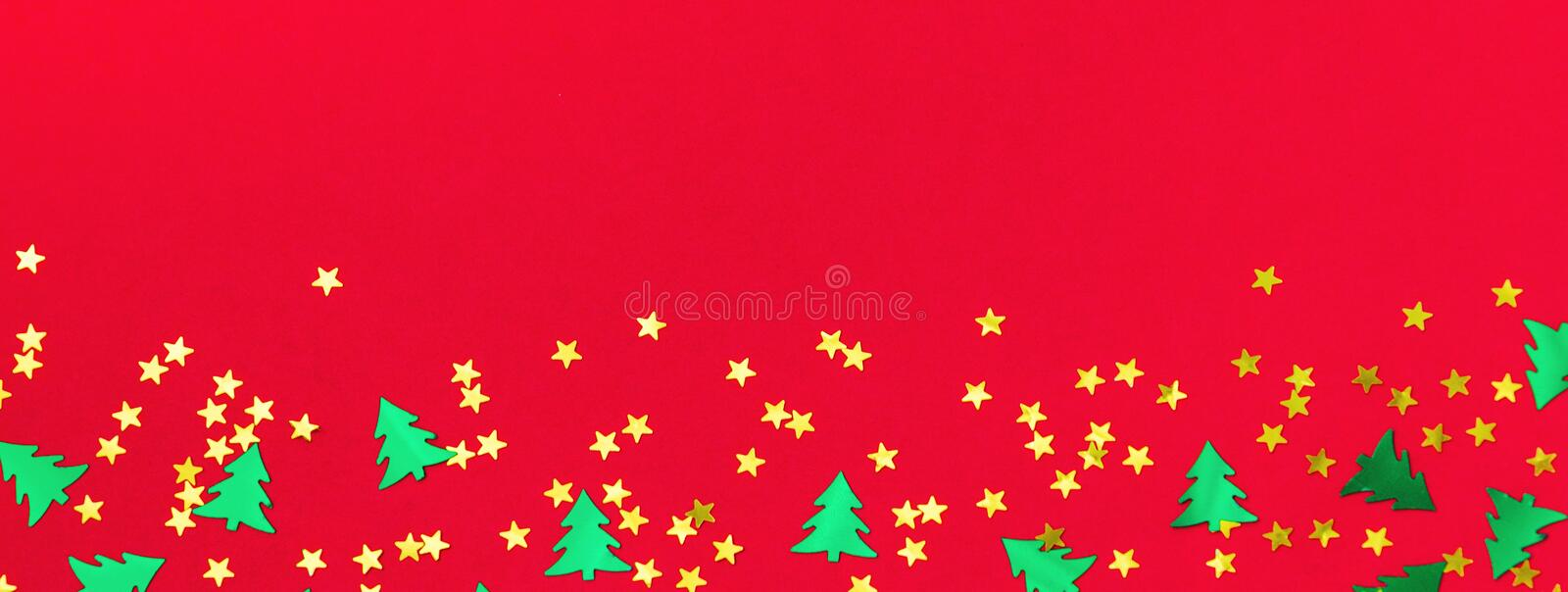 Christmas and Happy new year banner. Green metallic foil christmas trees and gold stars confetti on red background. Simple holiday design template. Frame with royalty free stock photography