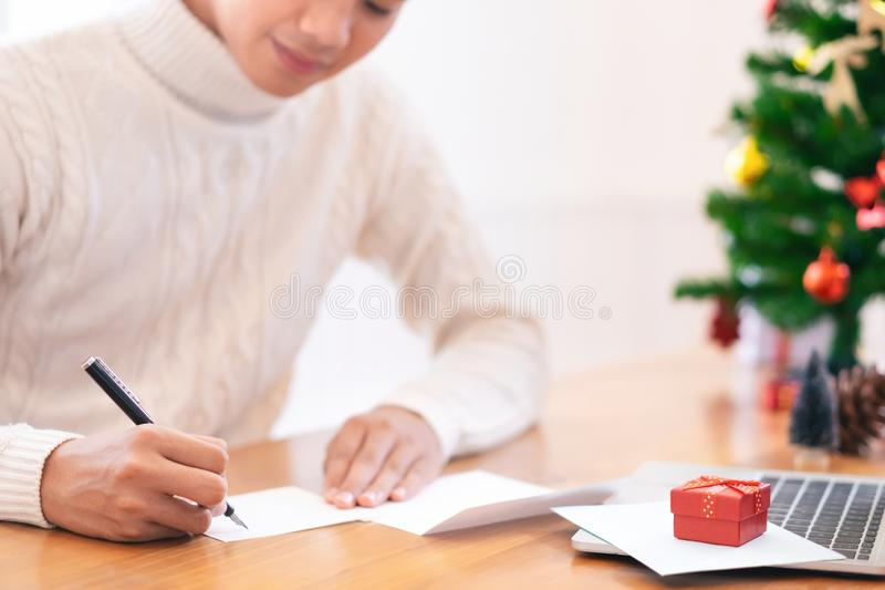 Christmas and Happy New Year blessing concept. Man wearing white sweater writing and sending greeting card.  stock photos