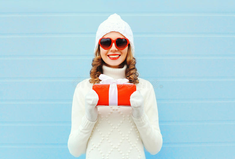 Christmas happy smiling young woman with gift box wearing knitted hat sweater sunglasses over blue background royalty free stock images