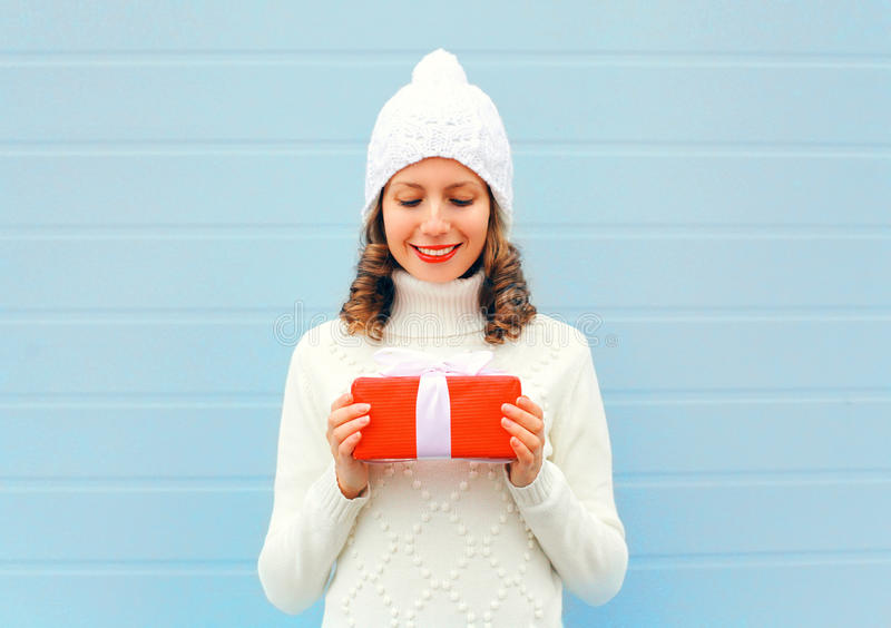 Christmas happy smiling young woman holds gift box in hands wearing a knitted hat sweater over blue stock photo
