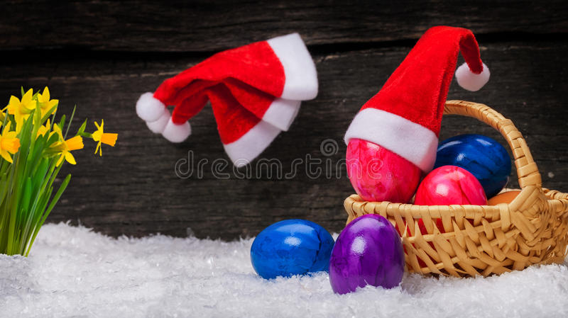 Christmas Hats, Easter eggs, daffodils. In snow royalty free stock photos