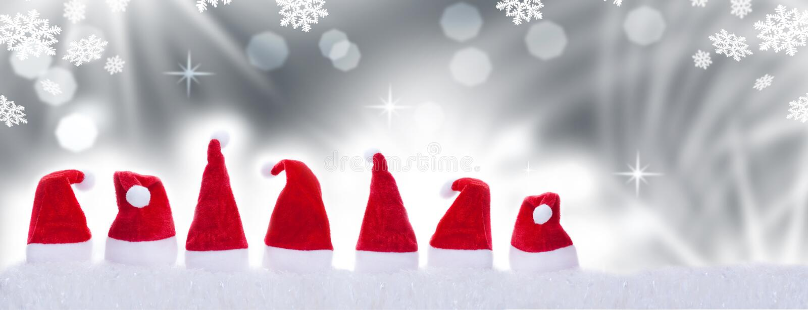 Christmas hats in front of bokeh. Seven christmas hats in front of bokeh royalty free stock photography