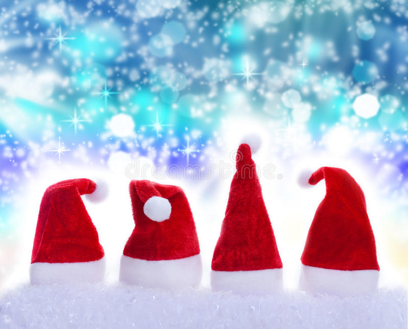 Christmas Hats, snowflakes. Christmas Hats and snowflakes in front of blue background royalty free stock photography
