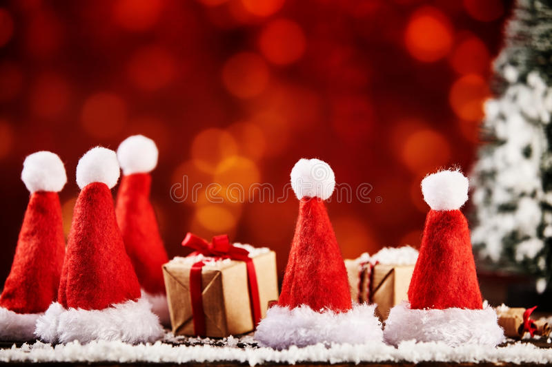 Christmas hats and wrapped xmas gifts or presents. For advertisement or party invitation stock photo