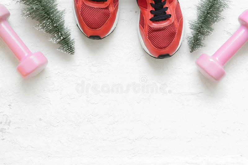 Christmas healthy acive lifestyle flat lay composition with sneakers, dumbbells, christmas tree on grunge white wood background. Merry Christmas and Happy new stock photography