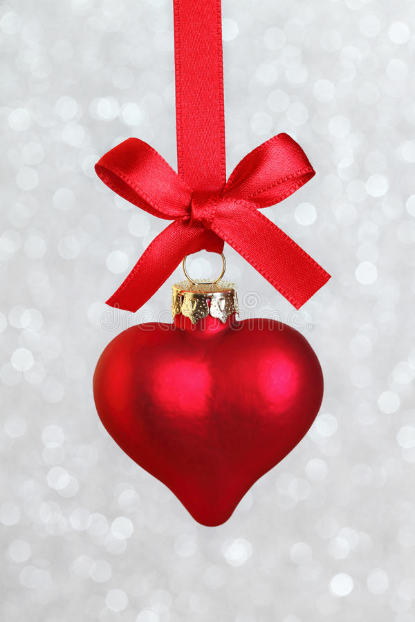 Christmas heart. Hanging with ribbon on silver background royalty free stock photos