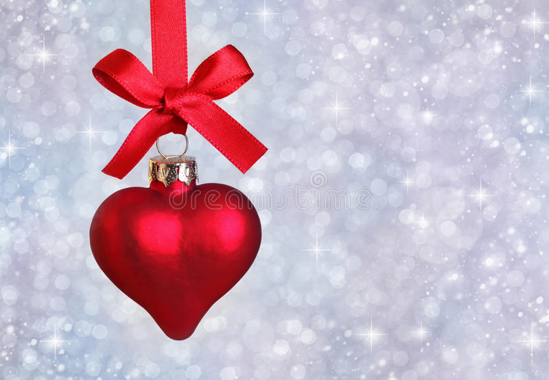 Christmas heart. Hanging with ribbon on silver background stock image
