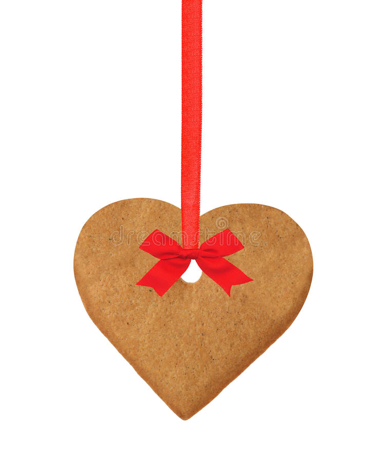 Christmas heart cookie on red ribbon with bow isolated on white. Background royalty free stock image